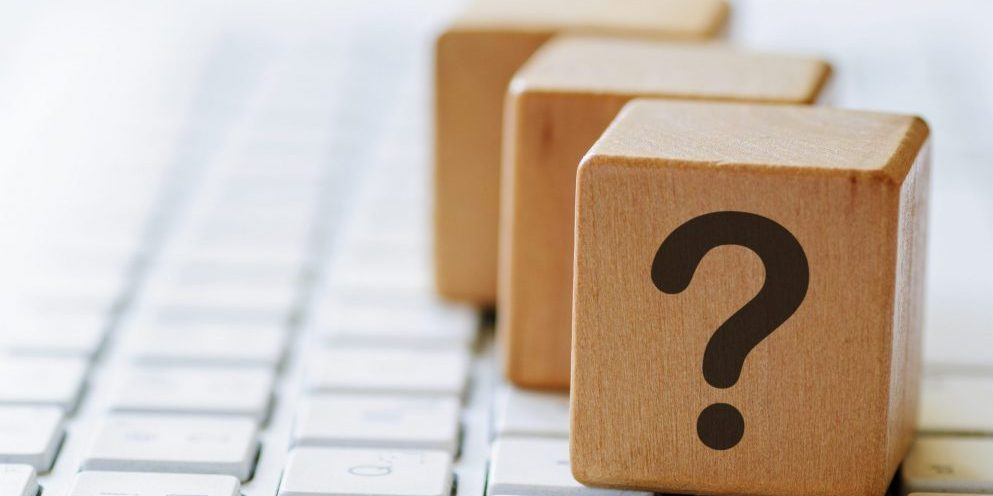 Small wooden dices with question mark on one side, sitting on computer keyboard and viewed in close-up with blurred copy space
